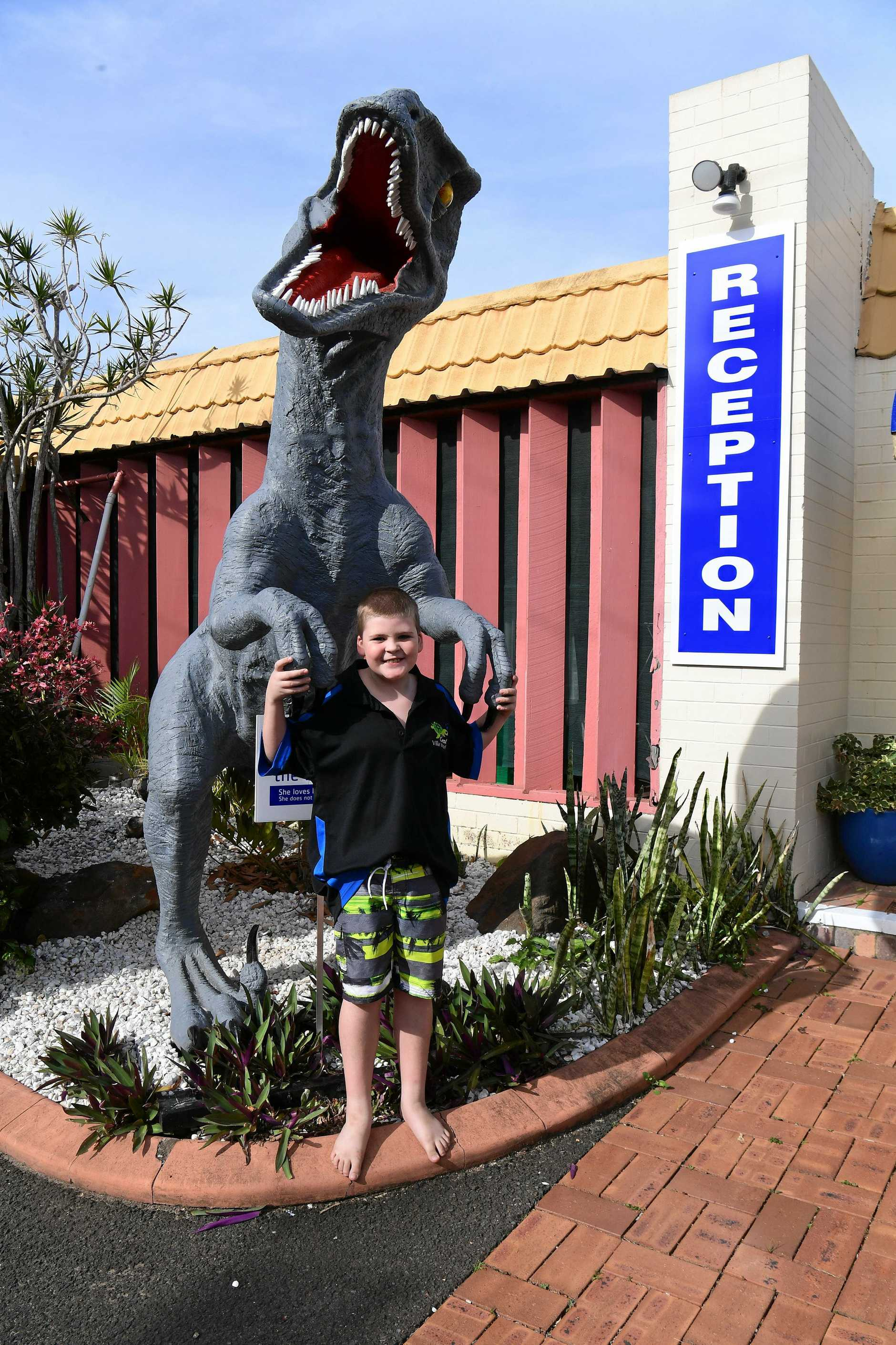 Charlie Rout with Roxy the dinosaur outside the Coral Villa Motel.