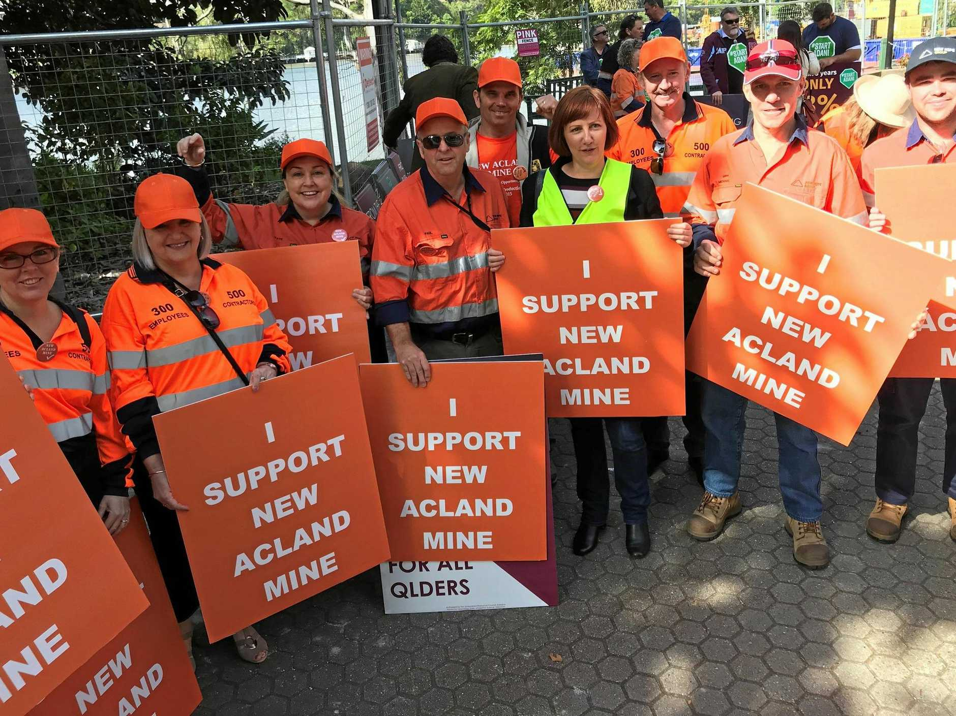 Toowoomba and Surat Basin Enterprise CEO Ali Davenport (in yellow) is flanked by supporters of New Acland Mine at the Queensland Day rally in Brisbane.