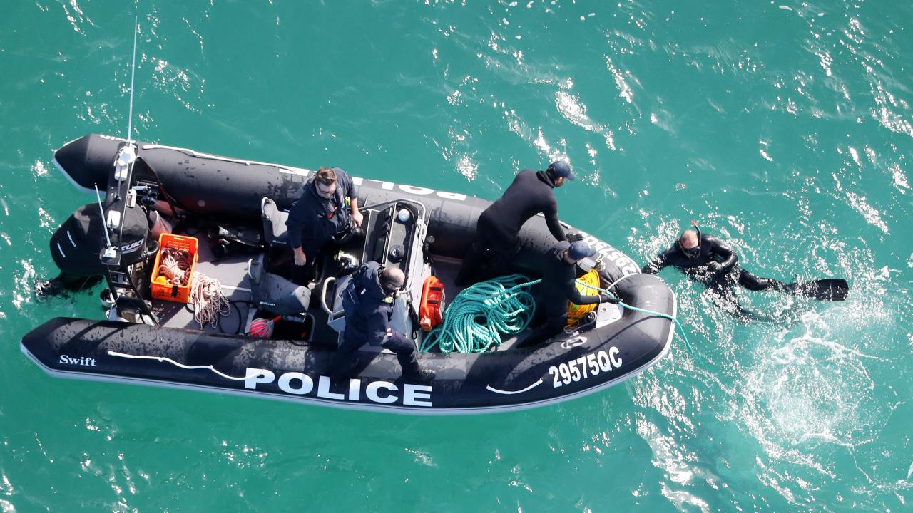 Police divers in action at the search scene. Picture: NIGEL HALLETT