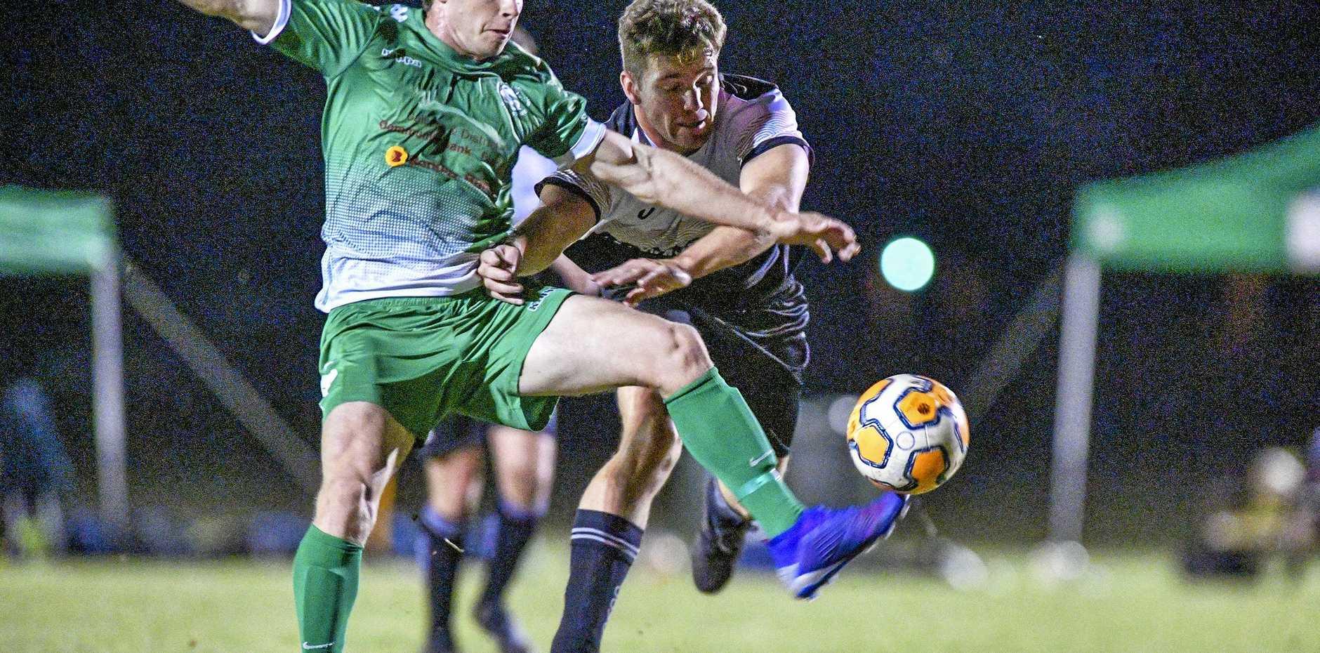 Clinton FC's Samuel Roberts gets a pass way under heavy pressure from Central FC's Adam Eiseman last weekend.