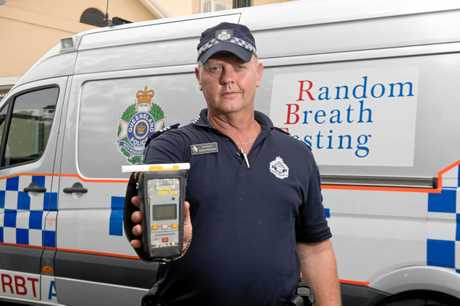 Mackay Road Policing Unit Sergeant Simon Robinson with a breathalyzer in front of the booze bus.