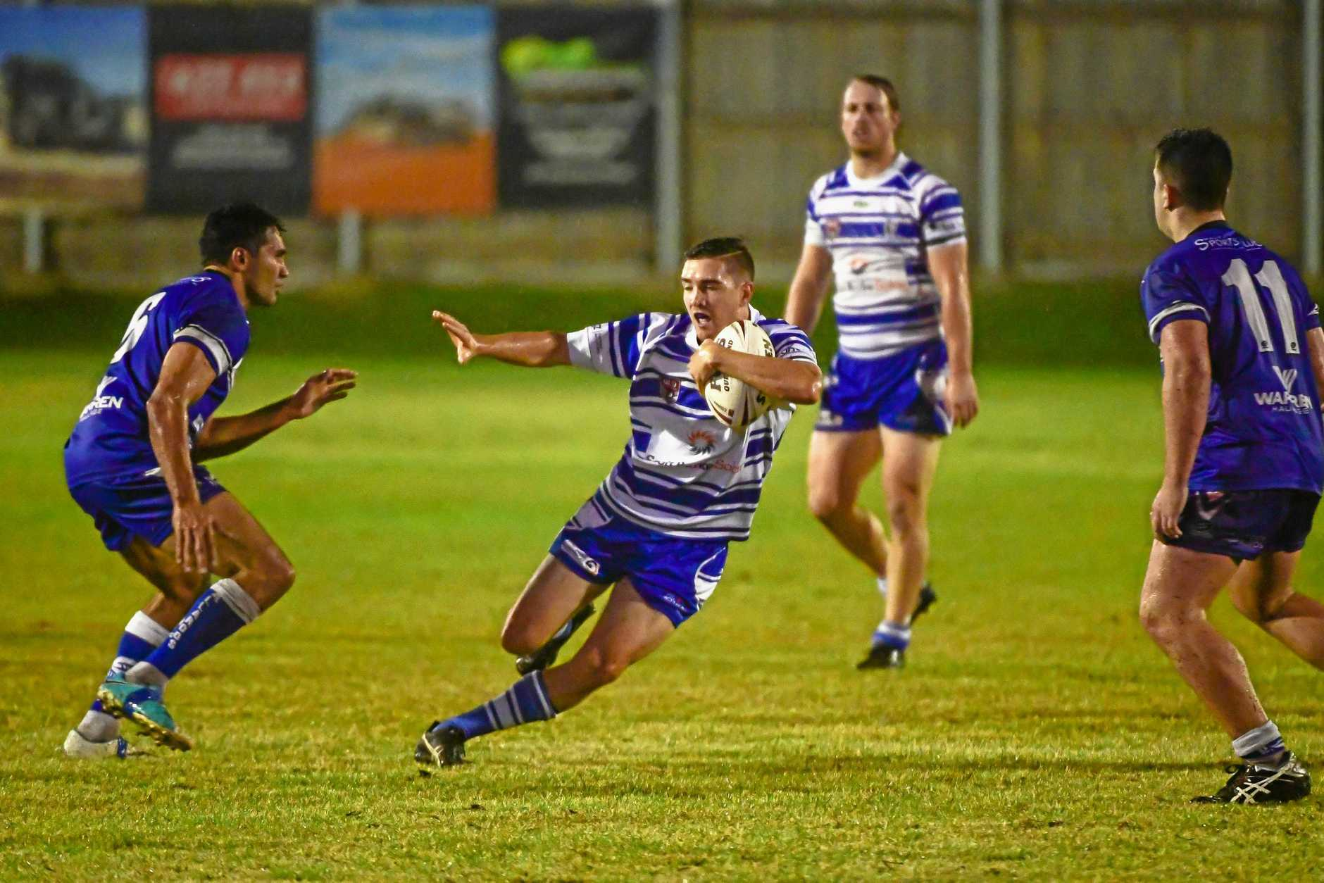 TFINDING THE SPACE: Past Brothers player Taylar Barritt weaves his way through the Wallaroos on Saturday night in Bundaberg.
