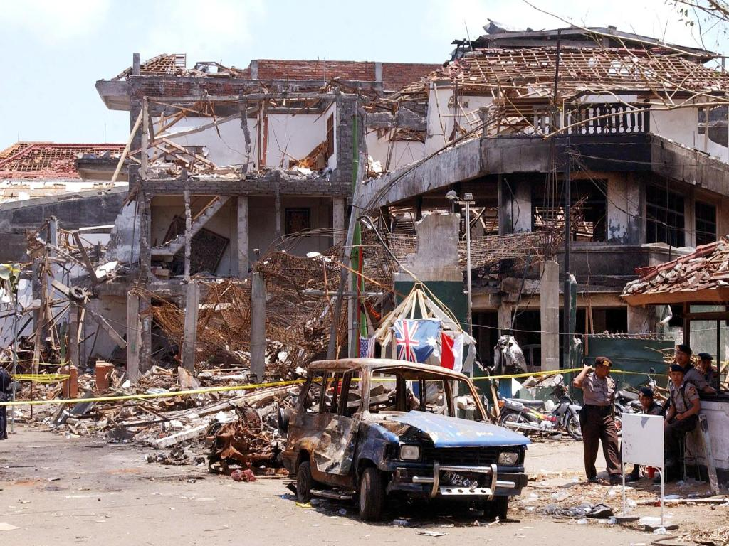 Forensic police officers and wreckage of car at the scene of Sari Club nightclub blast in Kuta in 2002. Picture: AFP