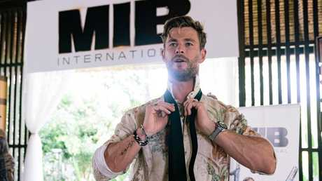 Chris Hemsworth gives master class on how to tie the iconic MIB tie. Picture: Getty