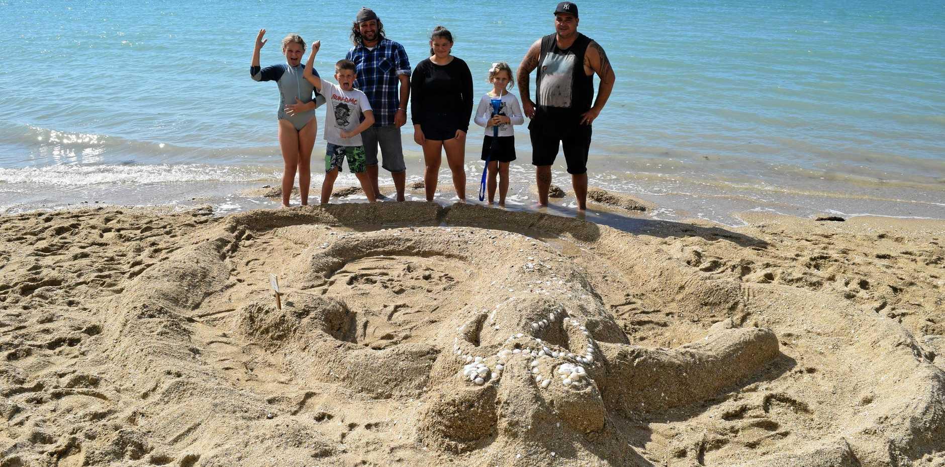 FAMILY FUN: Jubilee Pocket's Nevaeh Rimene, 11, Darius Rimene, 9, Kane Wheeler Ariane Rimene, 14, Buggy Williamson, 8, and Tom Rimene show off their sand sculpture of a tiki at Dingo Beach Whitfunday on Sunday.