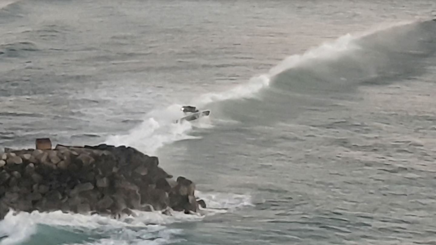 The moment one of the boats was overturned by a rogue wave.