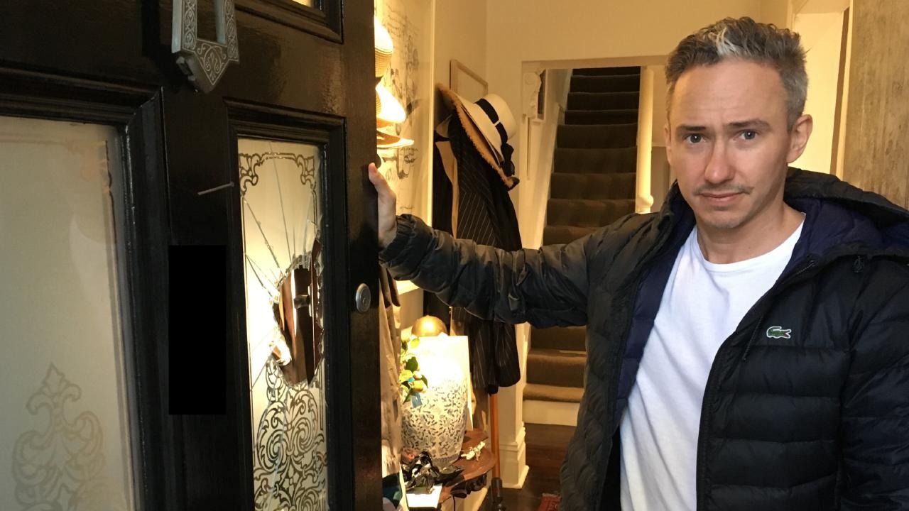 Eddie Madden next to the smashed door.