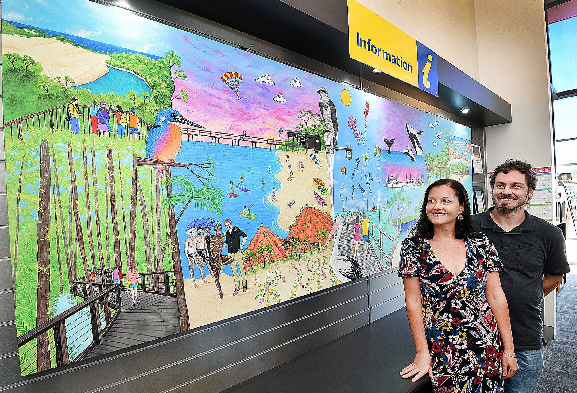 Hervey Bay Visitors Centre - artist Rebecca Jane Knowles and partner Matt Shirvington with the artwork she created for the newly renovated centre.