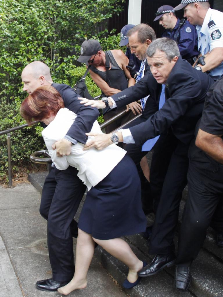 Former AFP cop Andrew Stark escorting then PM Julia Gillard after an Australia Day event turned hostile in 2012. Picture: Lukas Coch