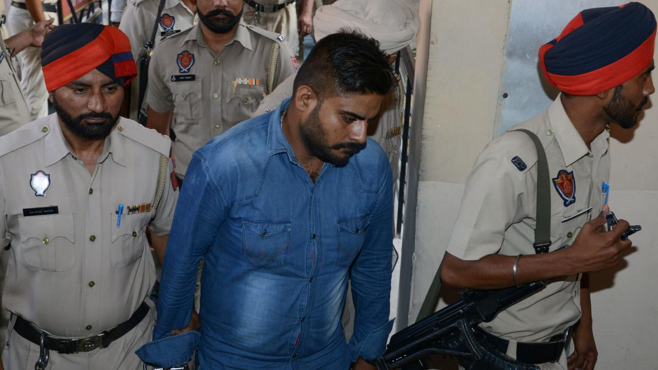 Indian Punjab Police escort Deepak Khajuria (C), who raped and murdered an eight-year-old girl. Picture: AFP