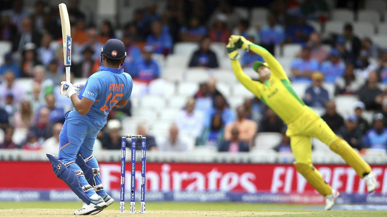 Alex Carey dives to catch out India's Rohit Sharma during the Cricket World Cup group stage match at The Oval. Picture: Nigel French/PA via AP