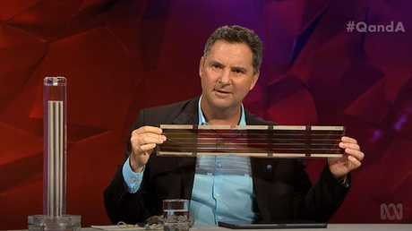 """CSIRO chief executive Dr Larry Marshall holds 3D printed solar cells, while a model """"hydrogen cracker"""" sits on the bench beside him. Source: ABC."""