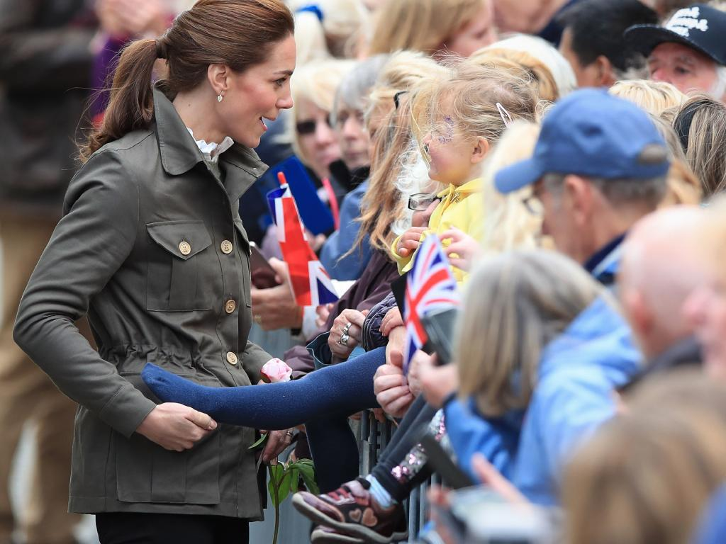 The casually dressed Duchess of Cambridge playfully grabbed the foot of Pearl Walker, 3, in the town centre during a visit to the Lake District. Picture: Peter Byrne/PA Wire