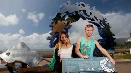 Gabriela Mendoza from Argintina and Aymeric Hamel from France inspecting the Citizens of the Great Barrier Reef statue on the Cairns Esplanade. PICTURE: STEWART MCLEAN