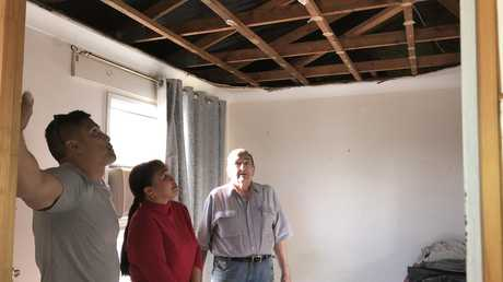 Builder Dean Morante inspects the damage to the inside of Ken and Elizabeth Harris's Shailer Park home.