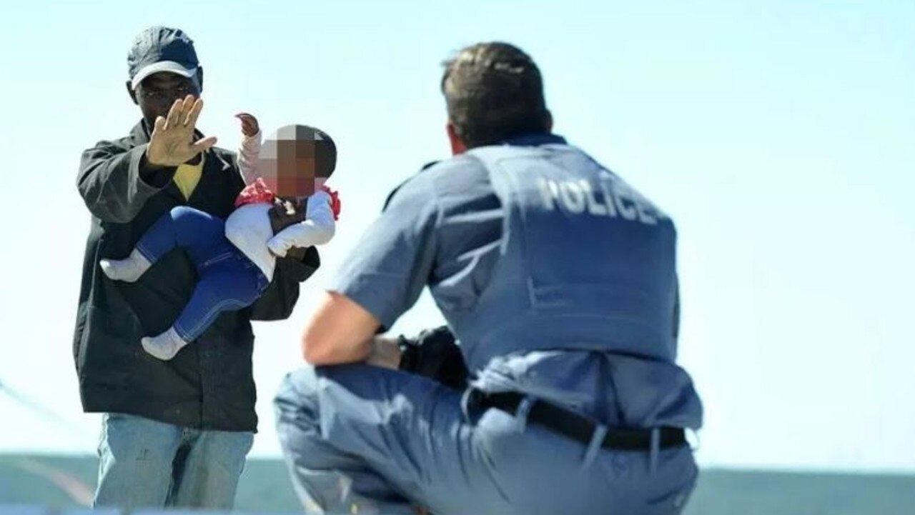 A worried police officer tries to talk the crazed father into releasing the child. Picture: South African Police Services