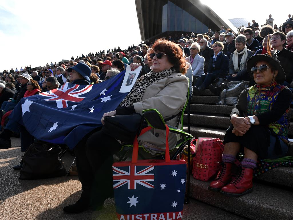 Members of the public watch the memorial service from the steps of the Opera House. Picture: Dan Himbrechts