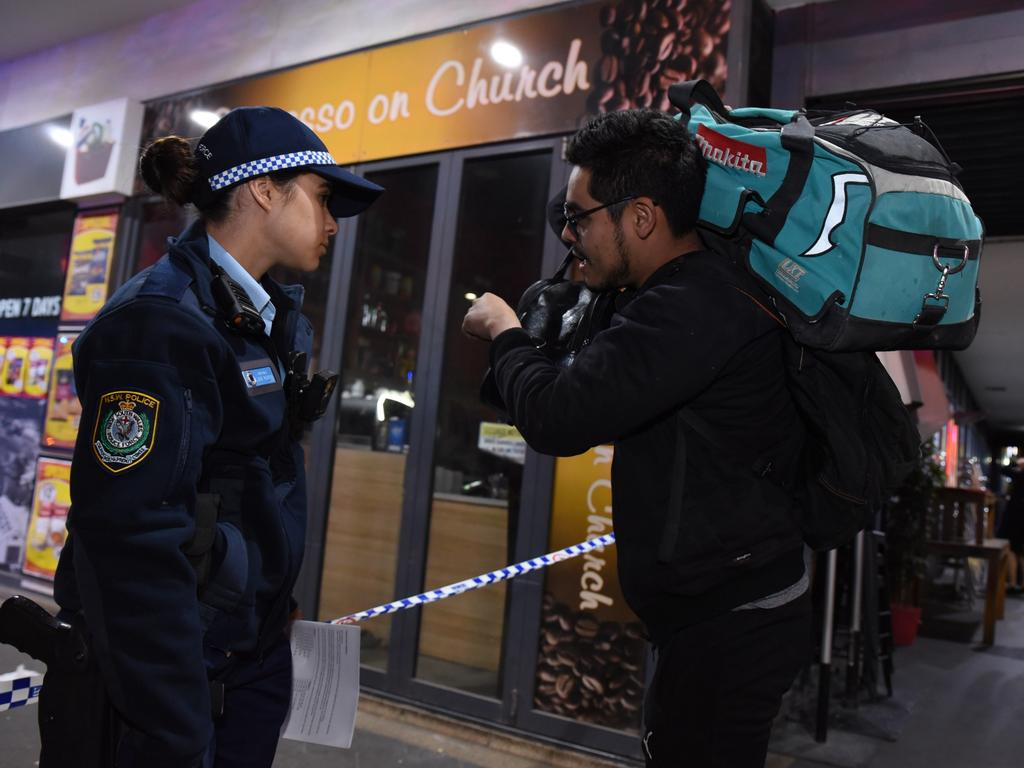 A resident talks to a police officer as authorities evacuate the complex. Picture: Flavio Brancaleone