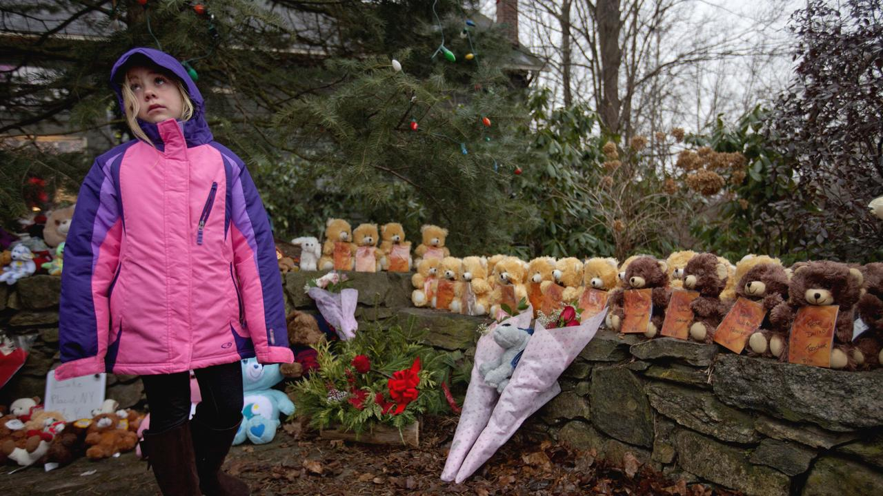 Ava Staiti, 7, visits a sidewalk memorial with 26 teddy bears, each representing a victim of the 2012 Sandy Hook Elementary School shooting. Picture: AP Photo/David Goldman