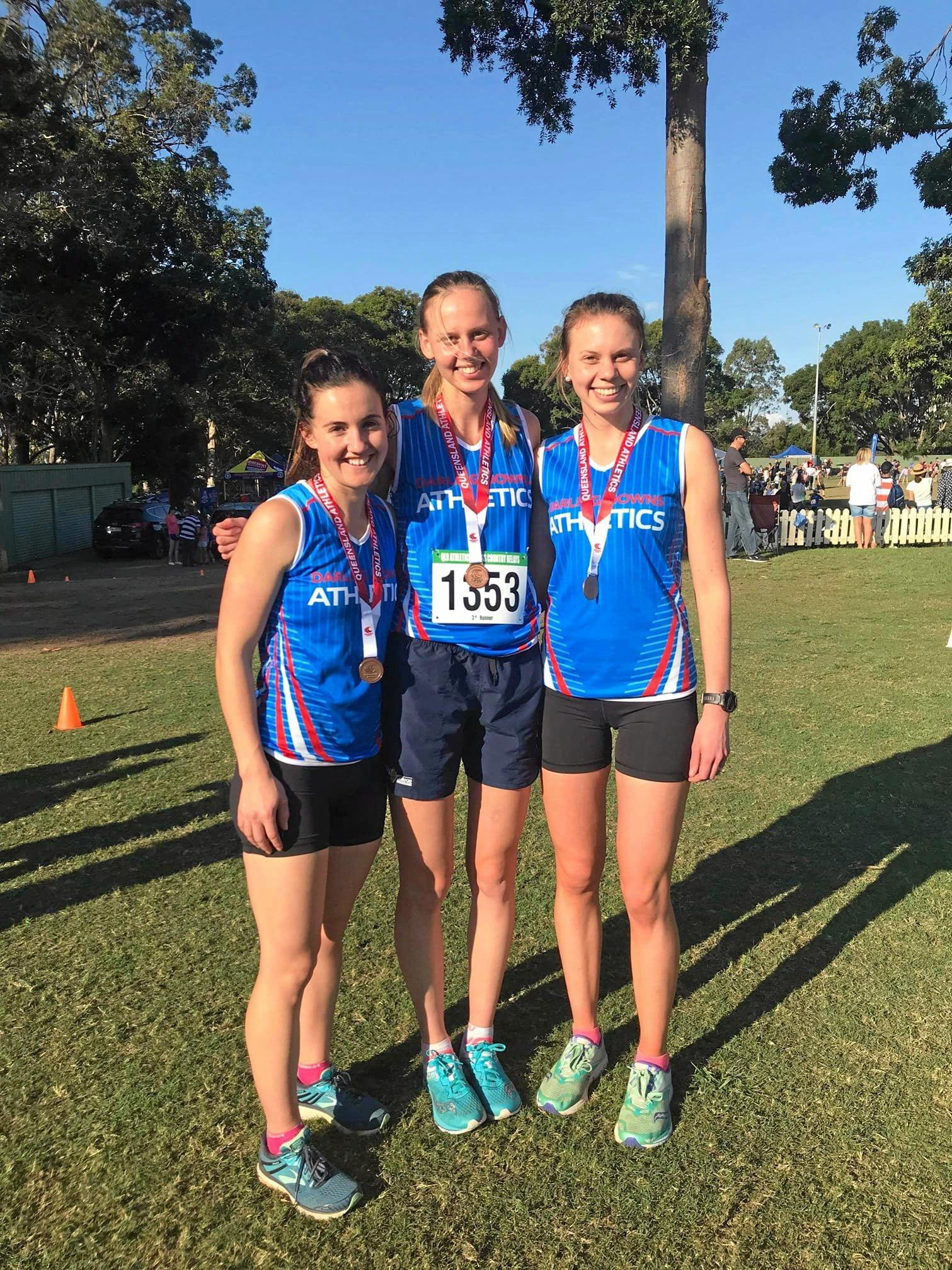 ALL SMILES: Darling Downs Athletics Club representatives (from left) Casey Richards, Lucy Young and Alex Young won a bronze medal in the open women's event at last weekend's Queensland Athletics Cross Country Relay Championships at Nudgee College.