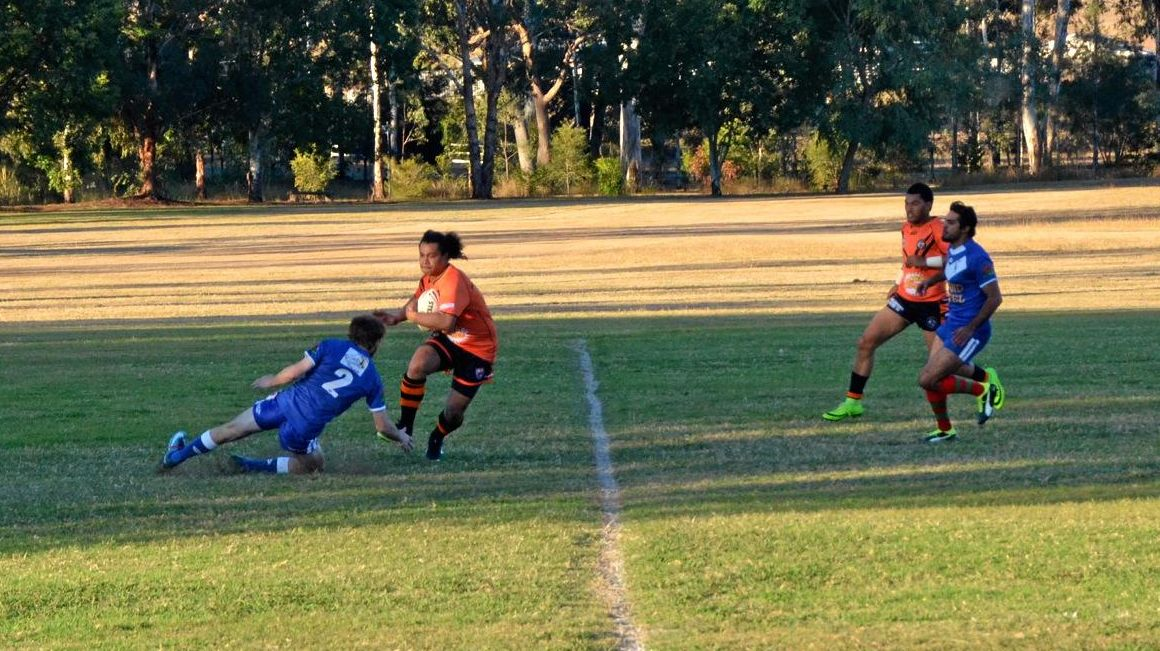 SIDESTEP: A Mundubbera Tigers player rounds a hapless Monto Roo on his way to the try line.