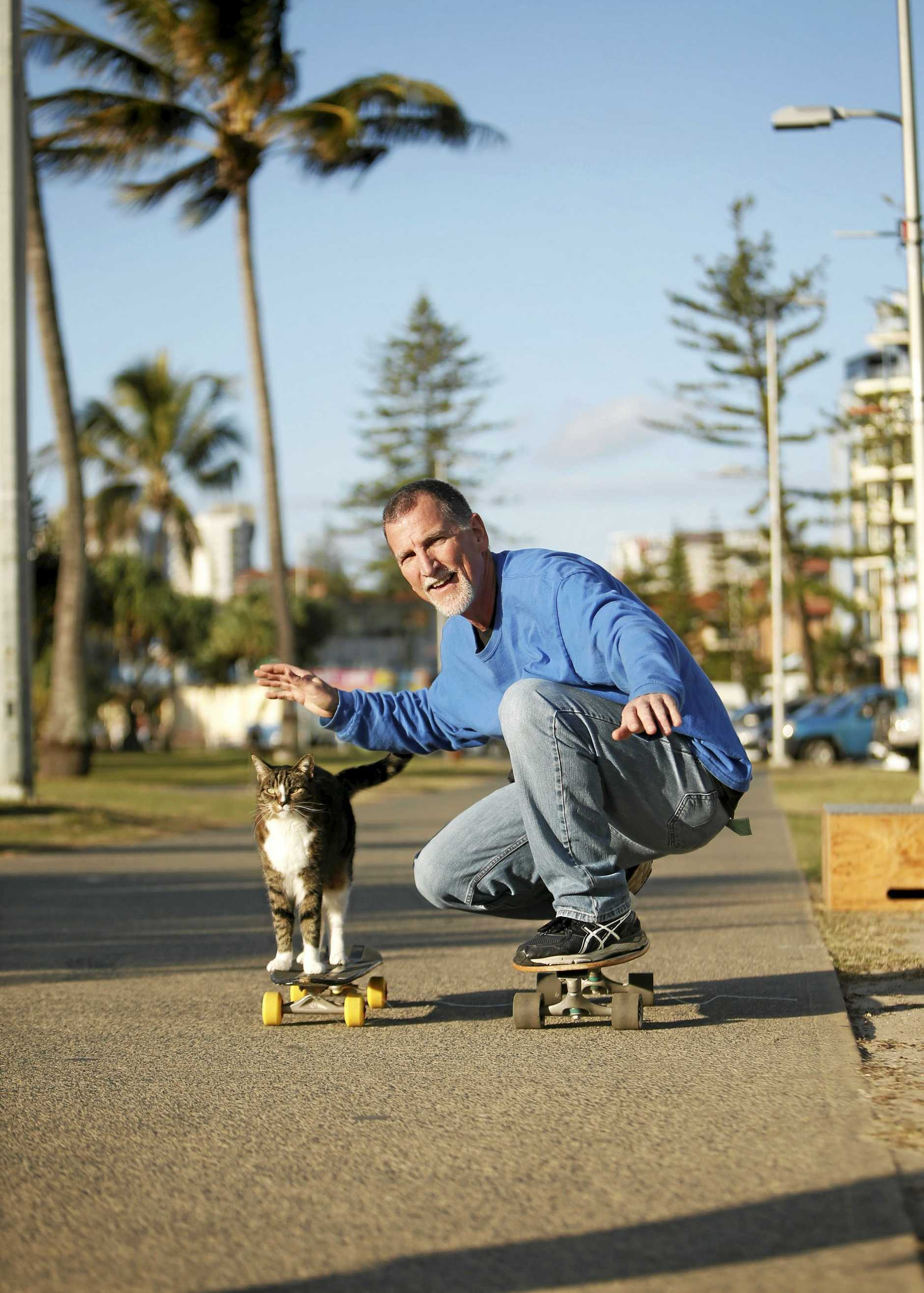 Didga the skateboarding cat with Tweed Heads trainer Robert Dollett.
