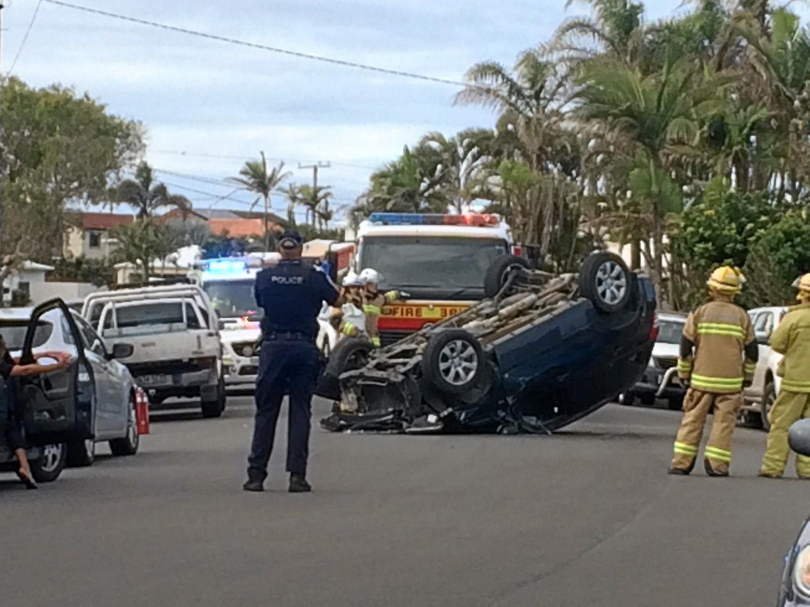A car is on its roof after it reportedly crashed into a parked car.