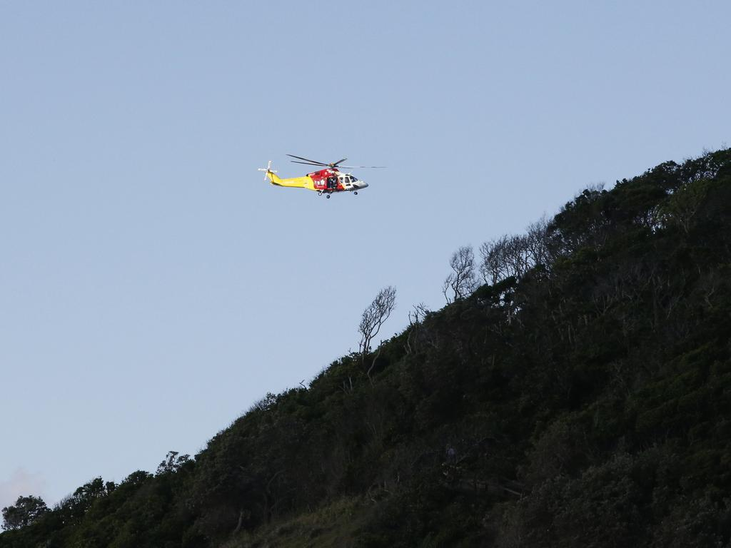 A search helicopter hovers over bushland near Watergos beach during a search for missing Belgian backpacker Theo Hayez. Picture: AAP Image/Regi Varghese