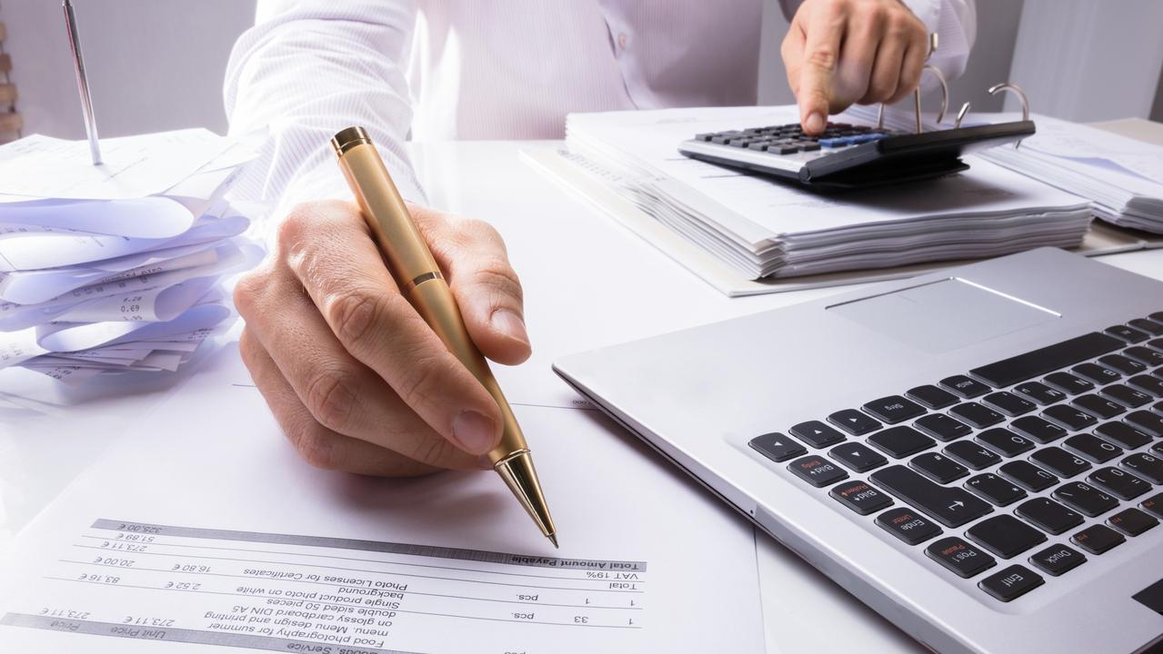 Accountant Calculating Invoice Using Calculator And Pen