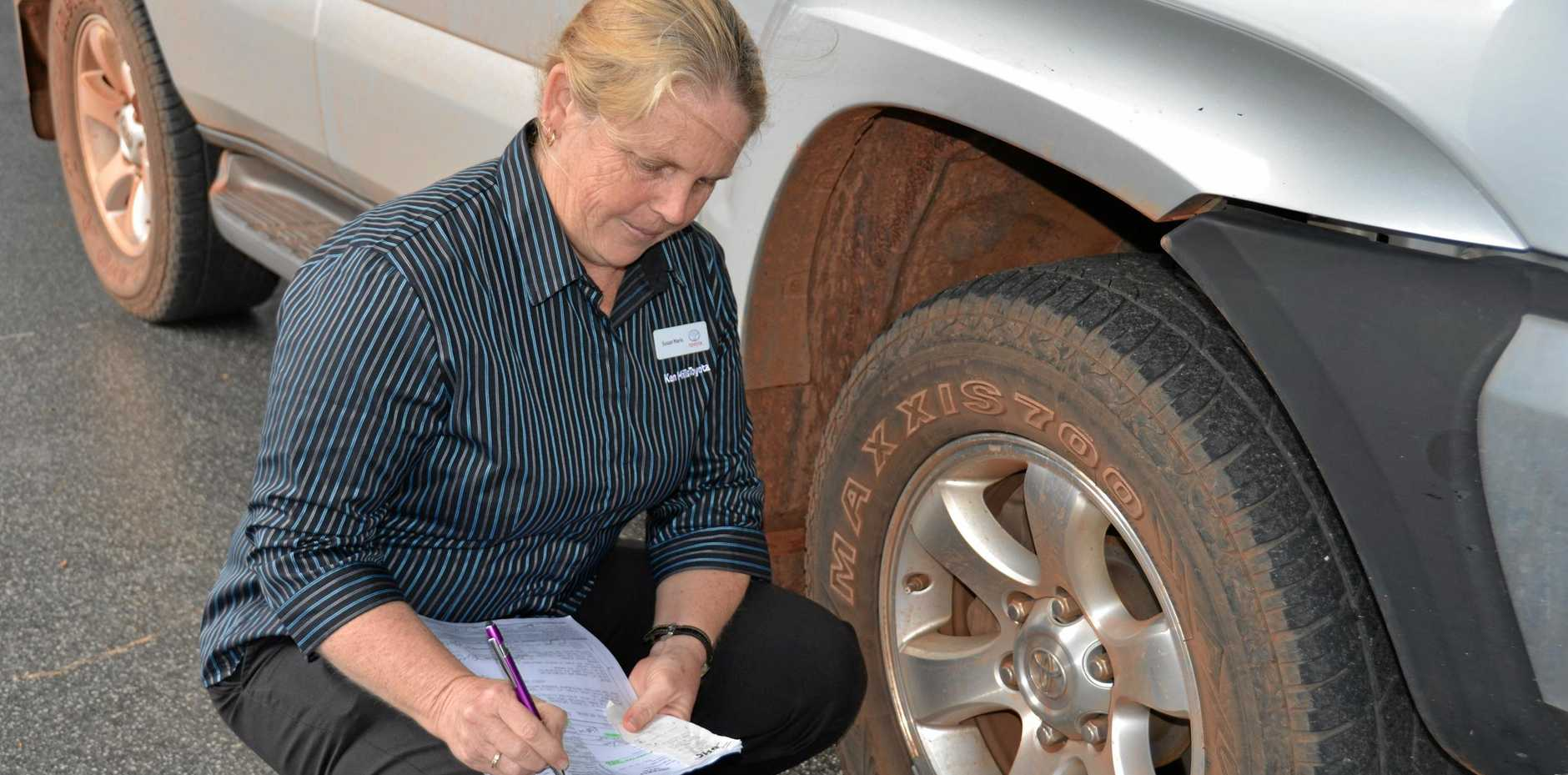 Susan Maris from Ken Mills Toyota inspecting a vehicle for maintenance.