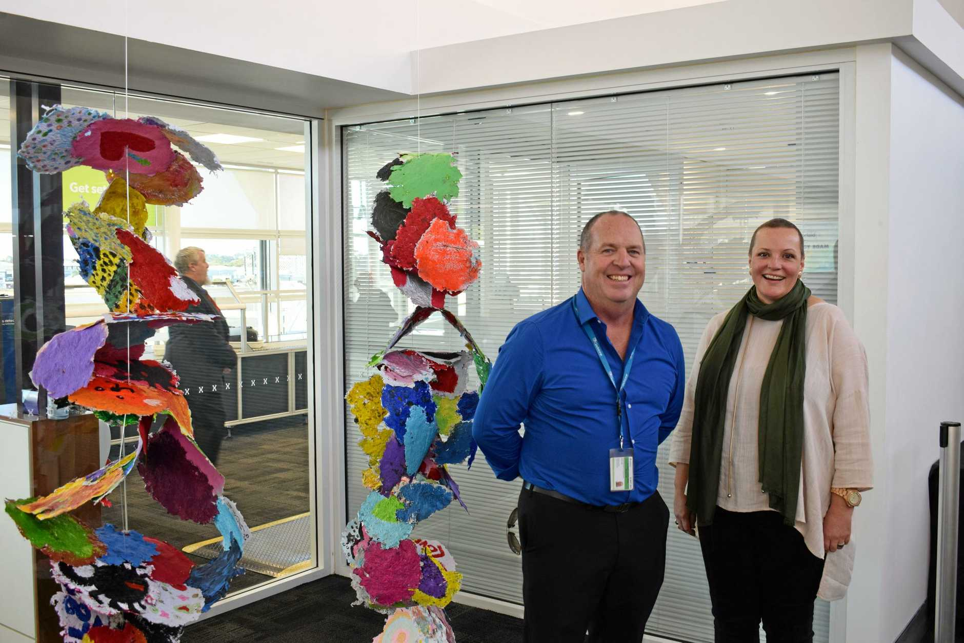Gladstone Airport Corporation acting CEO Peter Friel and A Country Arts Practice visual and community artist Melissa Peacock in front of the Community Arts Project made by Rosella Park School students on display at Gladstone Airport.