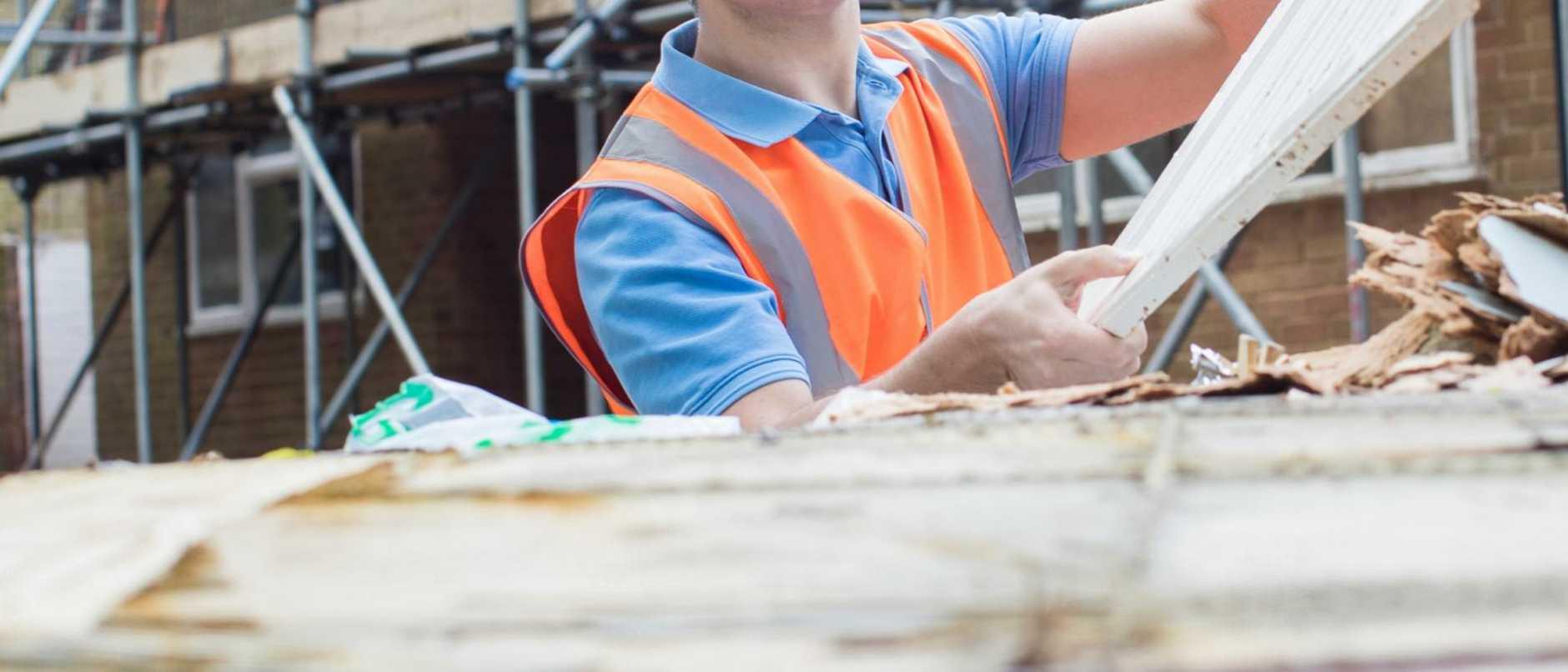 Builder On Site Putting Waste Into Rubbish Skip