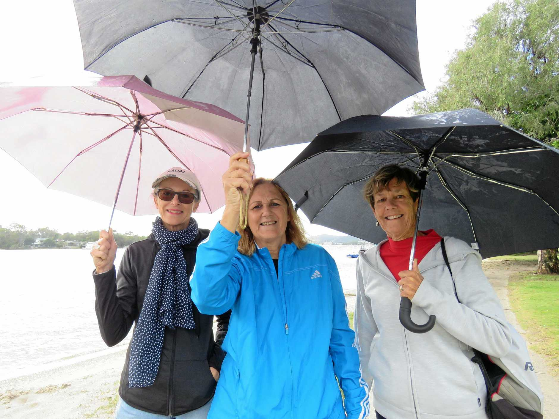 BROLLIES OUT: Delwyn, Sue and Marlene enjoy a stroll at the park along Gympie Terrace as the rain starts to recede.