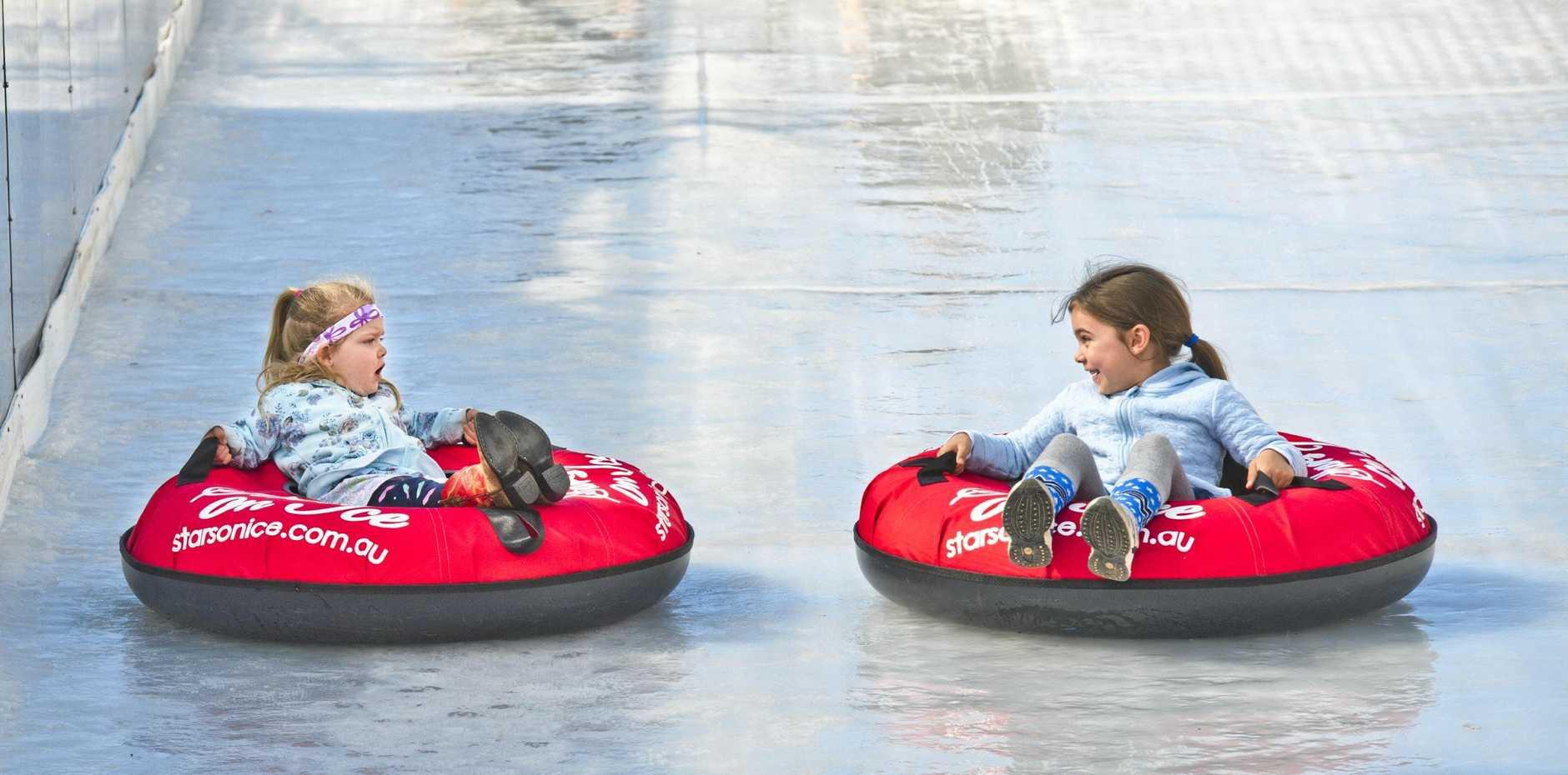 Sisters Mackenzie and Lexi Burlingham take on the Ice Slide at Winter Wonderland in Toowoomba.