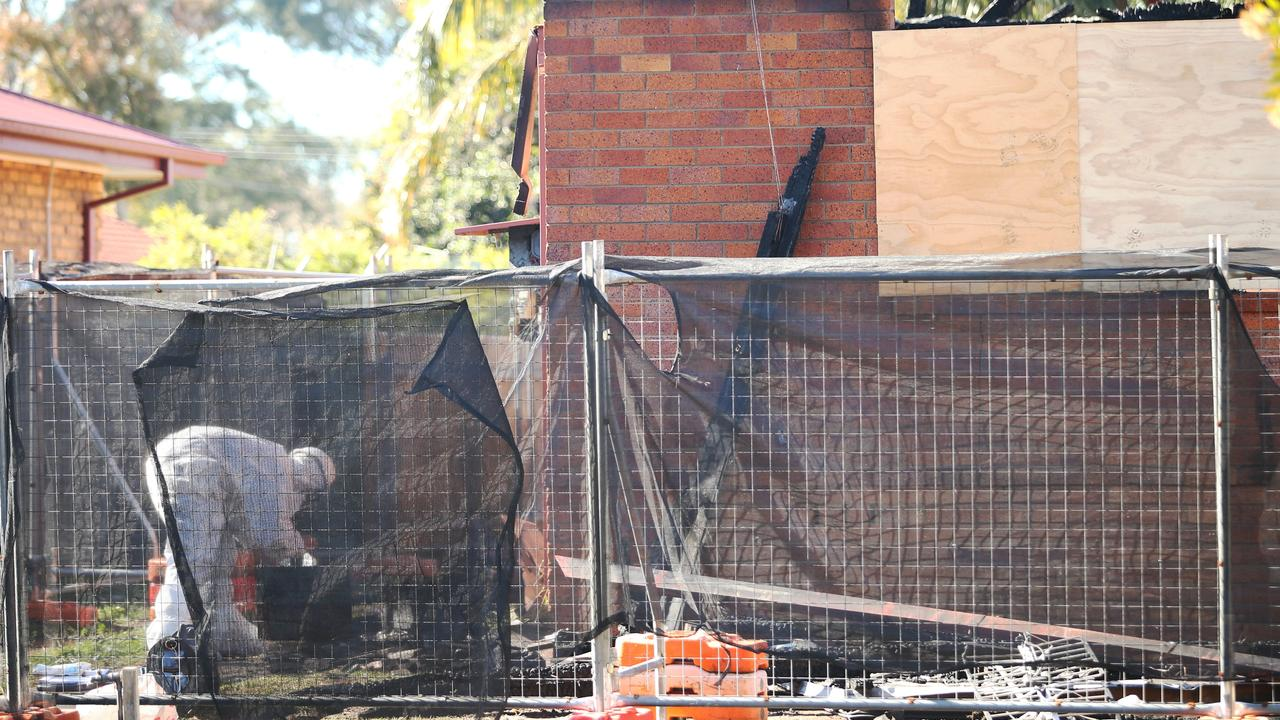 Contractors sift through the house ashes for hazardous materials. Picture: Peter Lorimer.