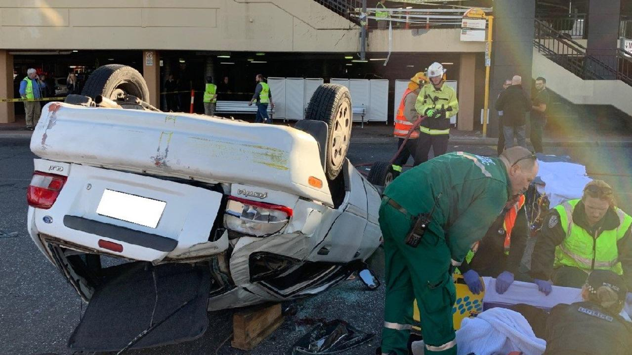 A car has landed on its roof after crashing through a barrier on the first floor of the Westfield Marion shopping centre car park. Picture: SA Police