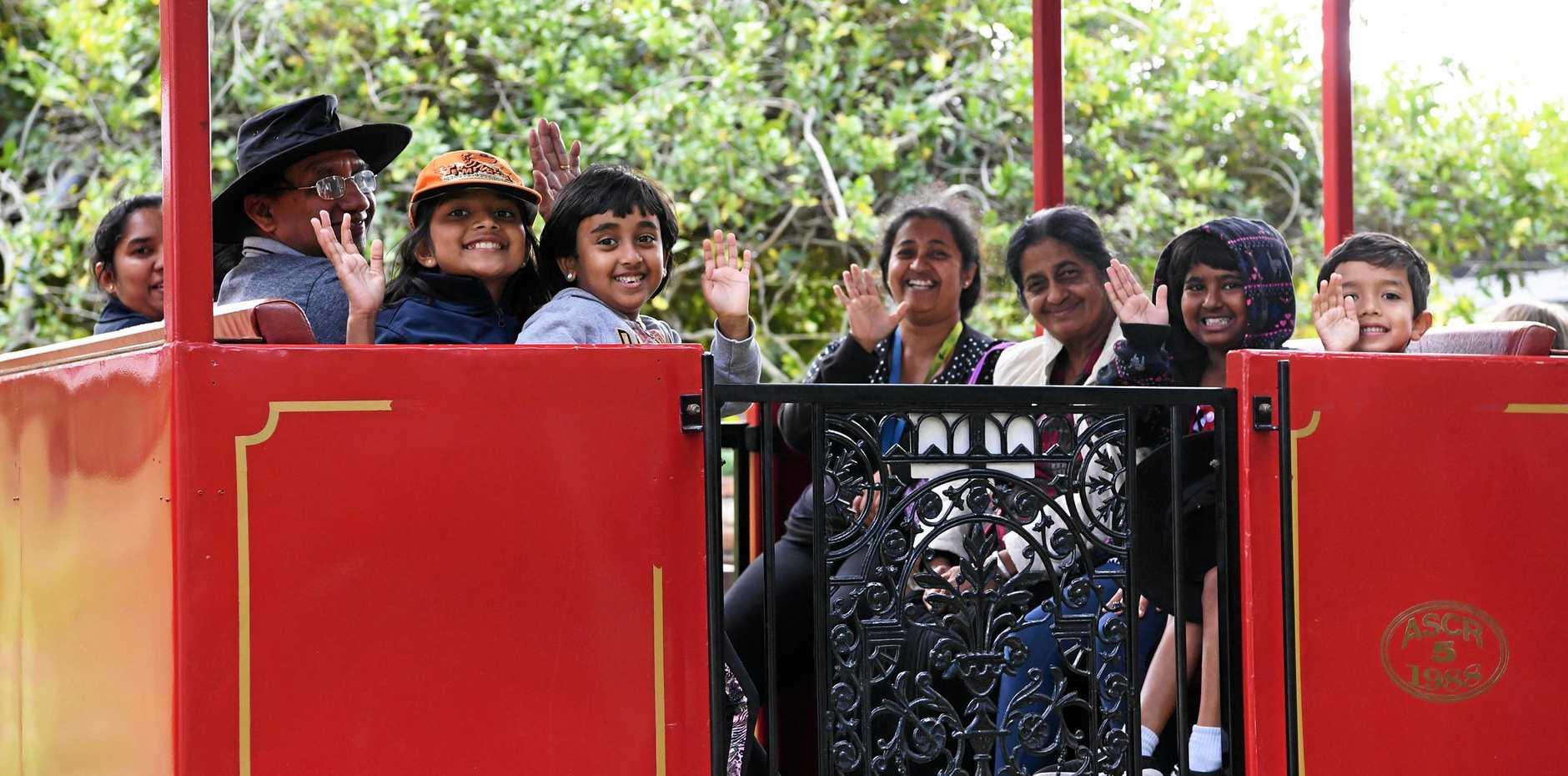 FAMILY HOLIDAY FUN: The Welagedara and De Silva families enjoying their outing on the Australian Sugar Cane Railway in the Bundaberg Botanic Gardens.