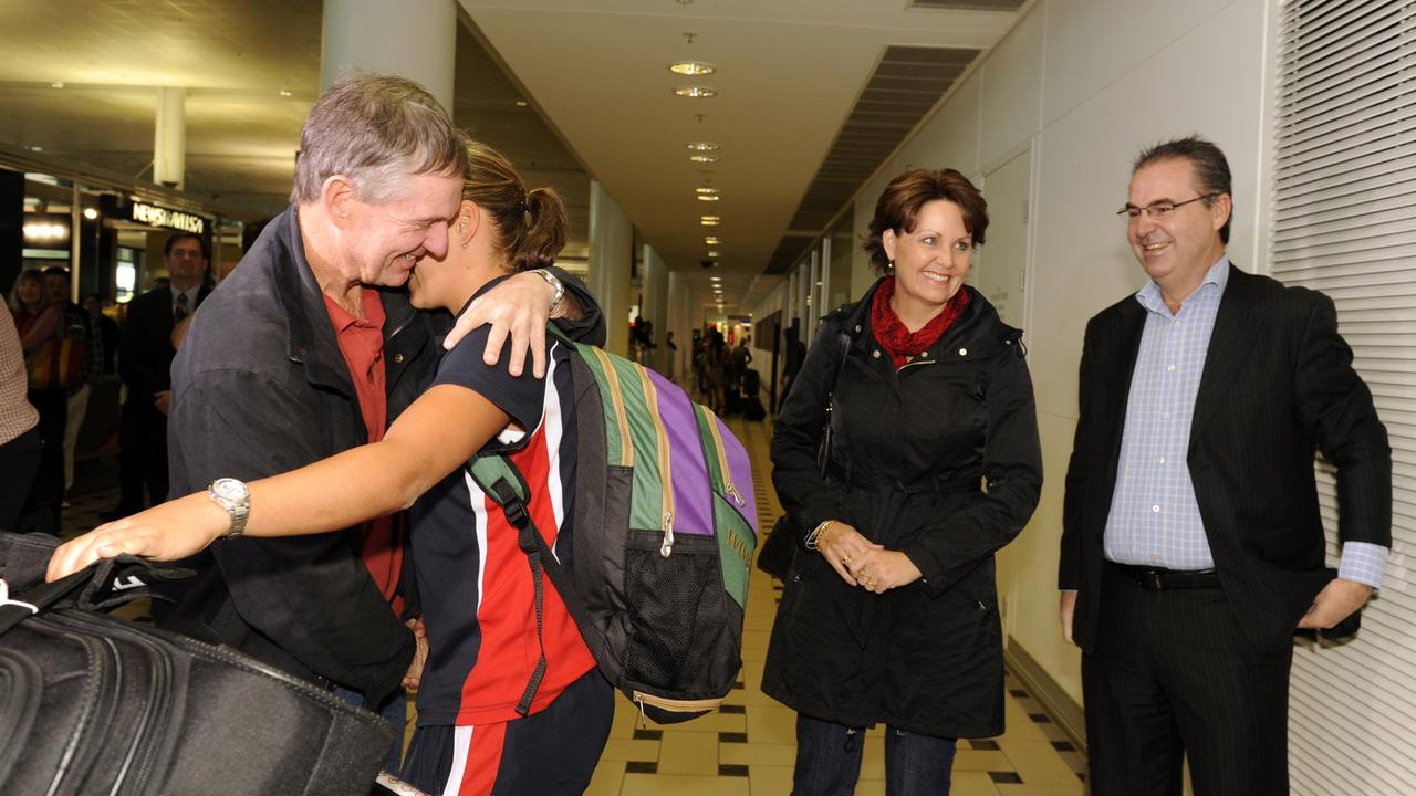Coach Jim Joyce gives Barty a hug at the airport as mum Josie and dad Robert look on.