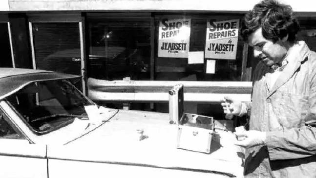 Senior Constable L. Jones examines a vehicle parked behind the Lennons Plaza Hotel on Burnett Lane. He's dusting for fingerprints.