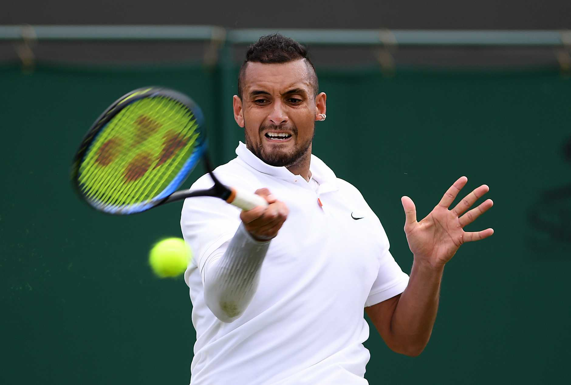 Nick Kyrgios fires back a shot in his first-round clash.