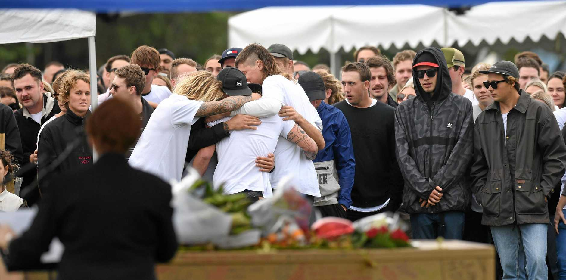 Friends and team mates comfort each other at the memorial  for 22-year-old Tim Watkins at the Mullumbimby Rugby League Club Grounds.