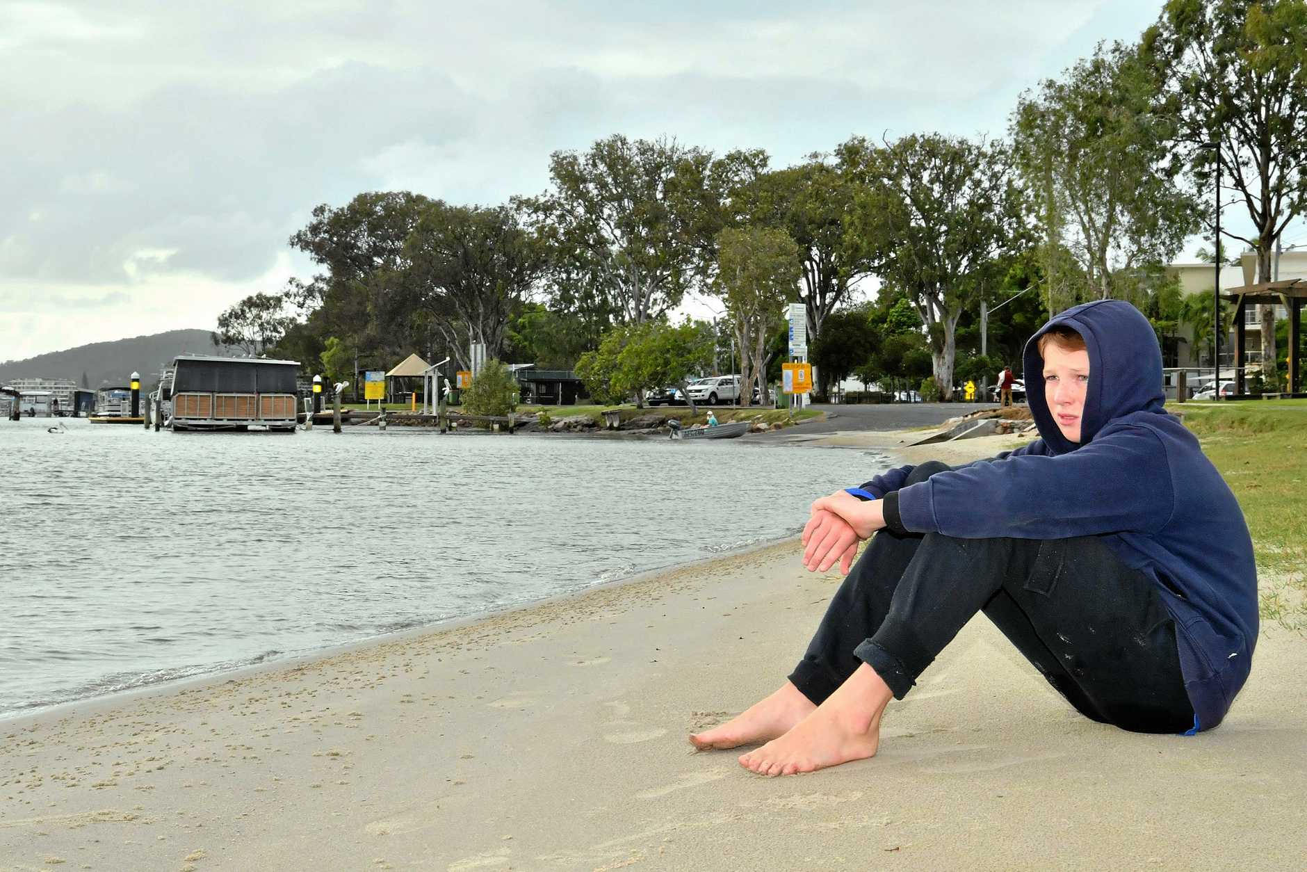 UPSET BOY: Angus Campbell, 14, sits along on Gympie Terrace where his tinnie was stolen.