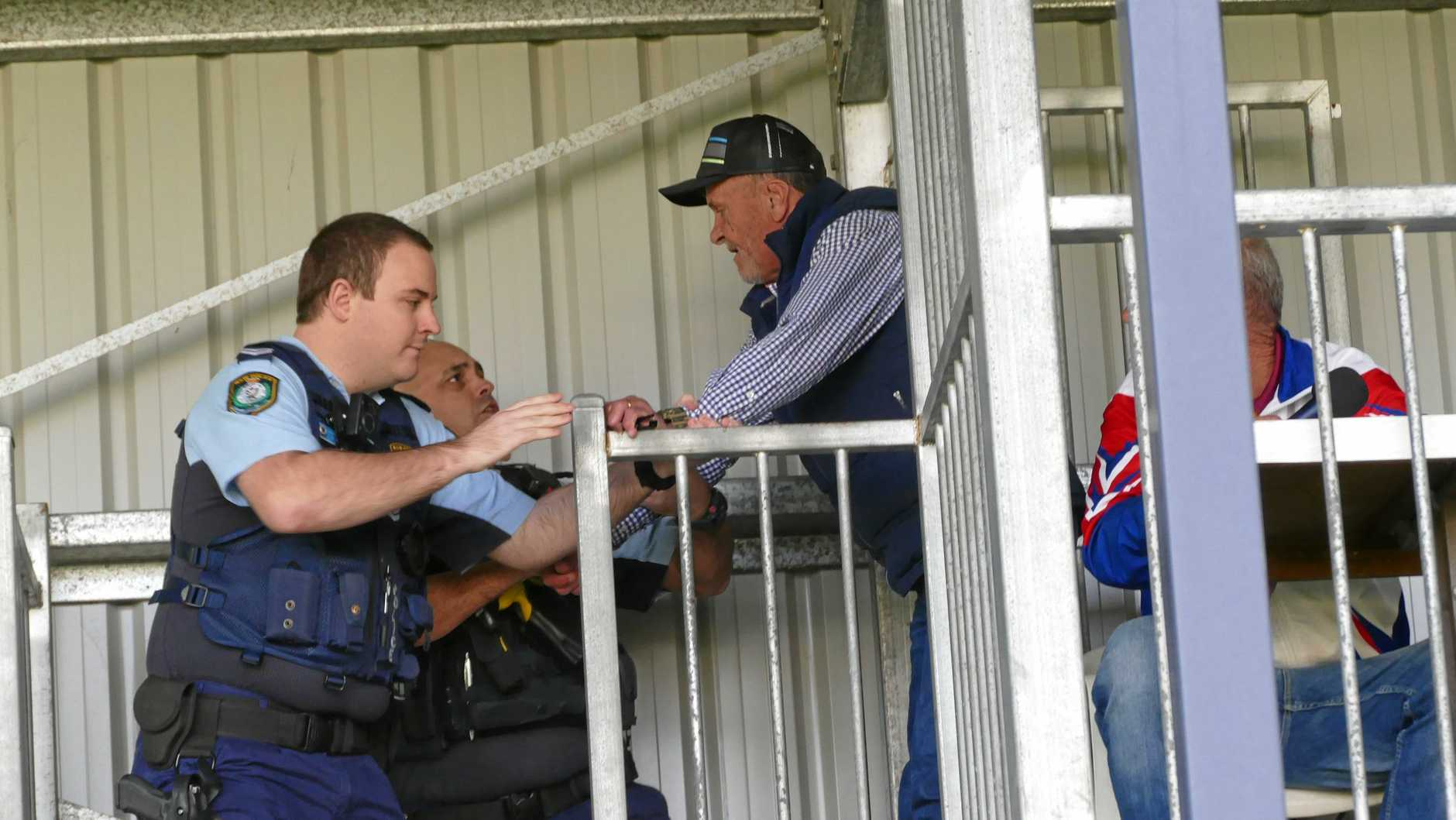 Two police officers confront Grafton Ghosts rugby league called in the commentary box at Saturday's game against Woolgoolga.
