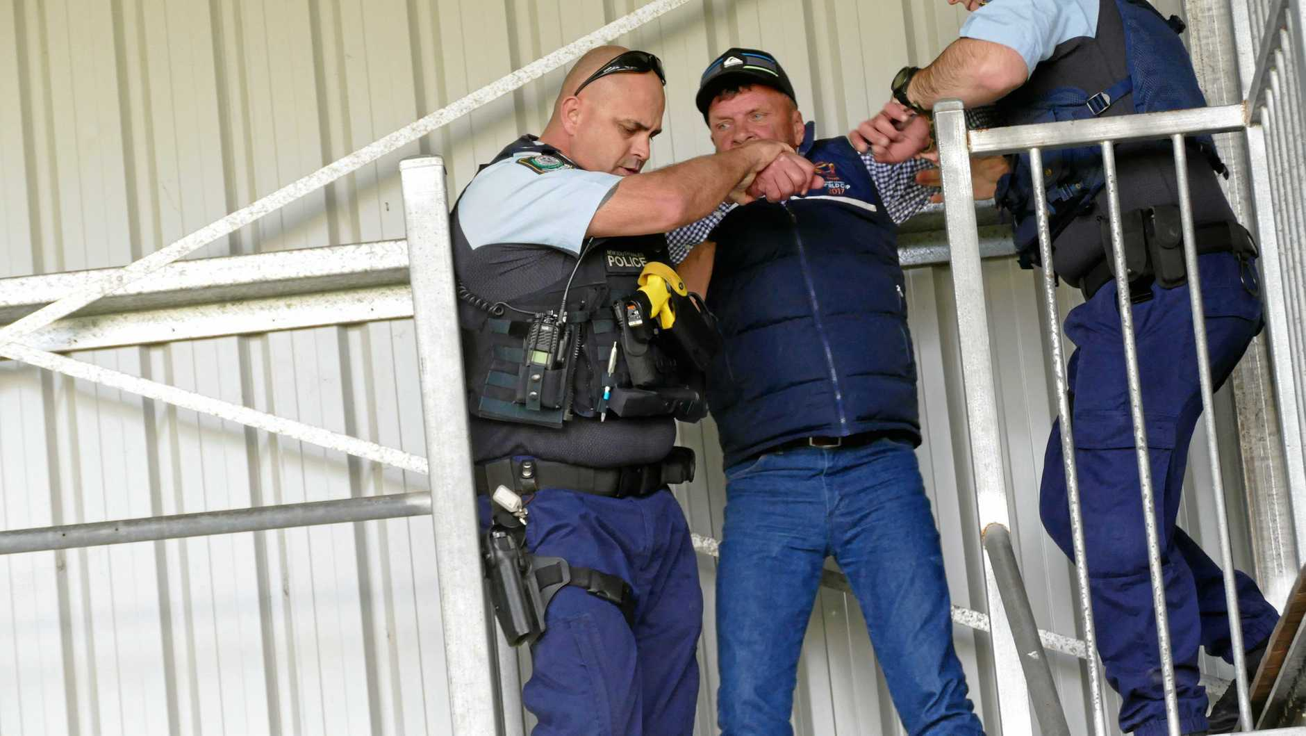 League caller Doug Graham struggles as police remove him from the commentary box at Frank McGuren Field on Saturday.