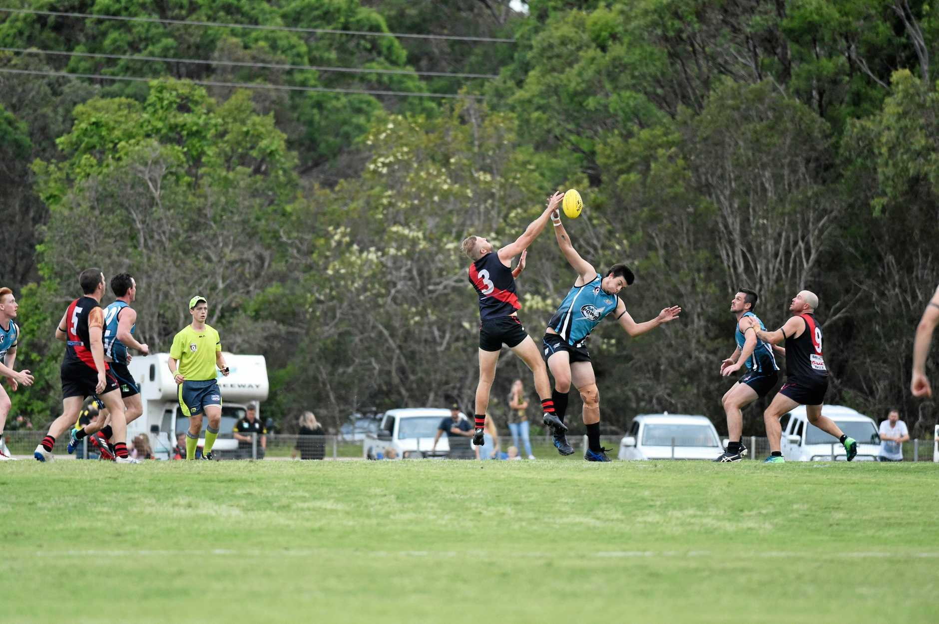 Hervey Bay Bombers Matthew Burgess hits the ball away from the ruck contest in the Anzac Day match against Bay Power.