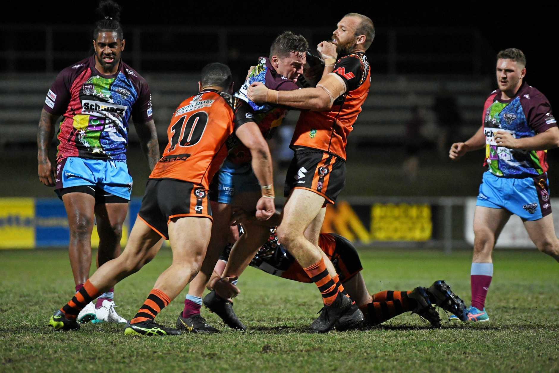 HARD HITS: Capras Ryan Jeffery tries to break through the East Tigers defence.