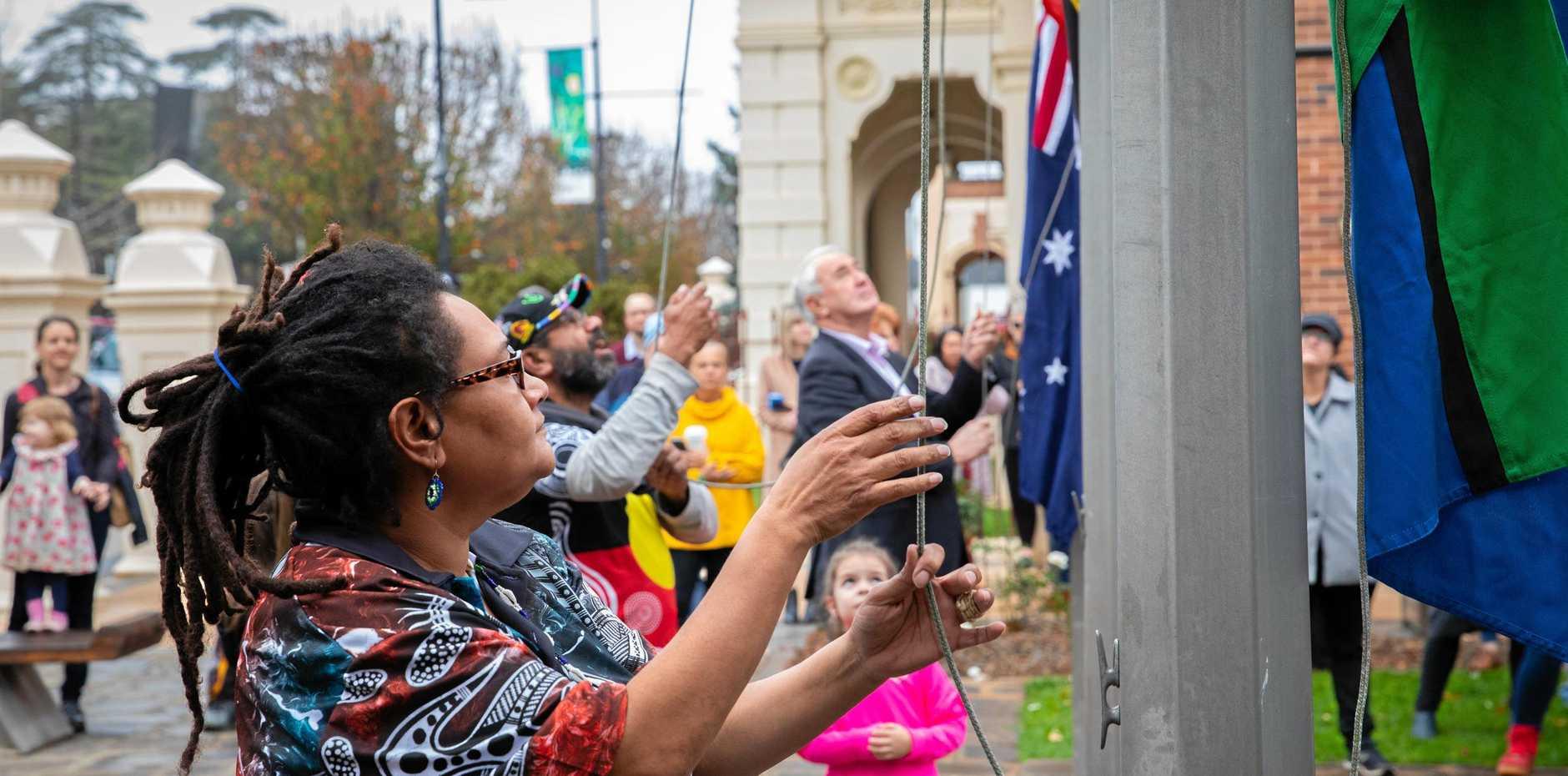 NAIDOC: Katie McLvor-Oui raises a flag at NAIDOC week celebrations yesterday.