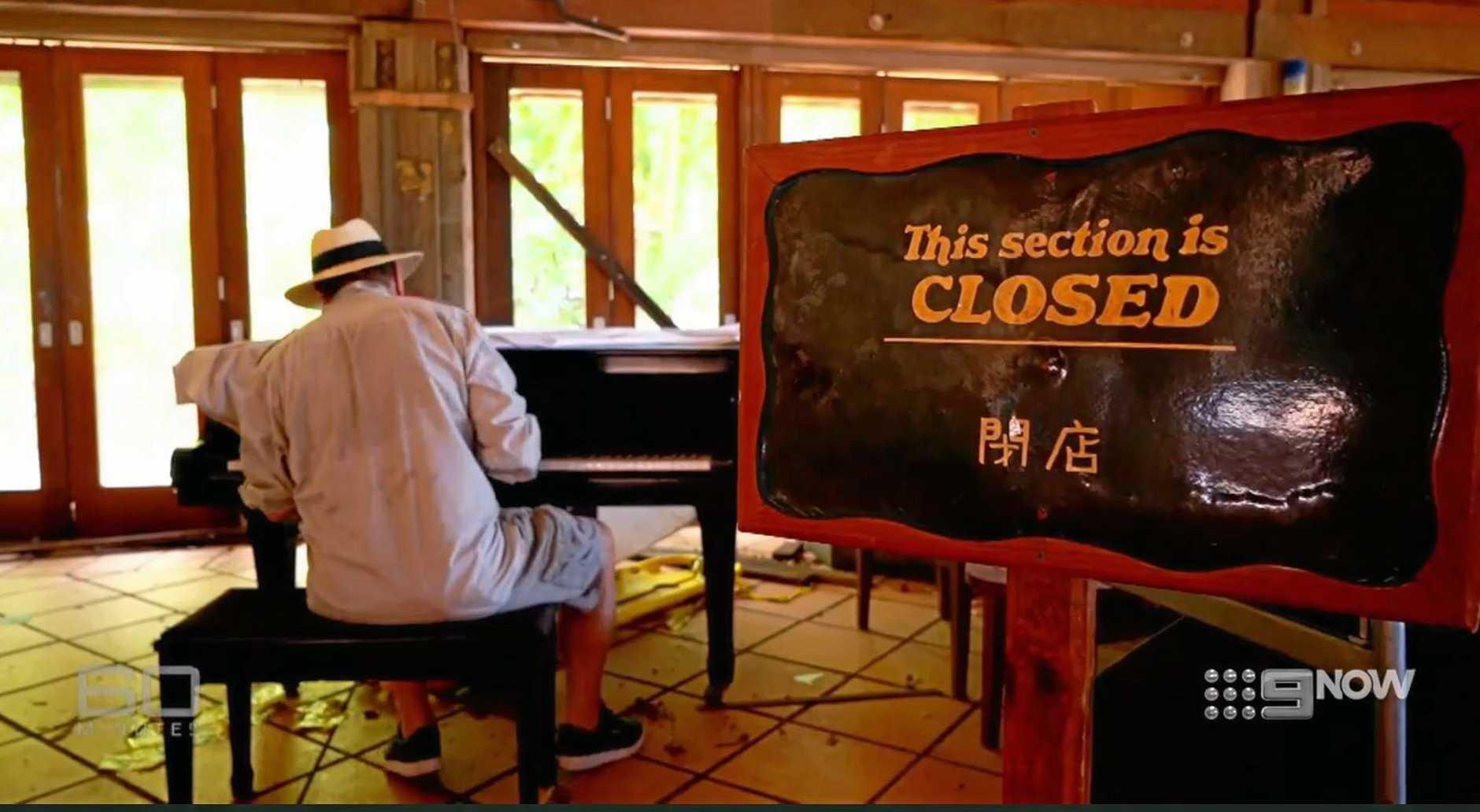 Charles Wooley at a piano on Lindeman Island.