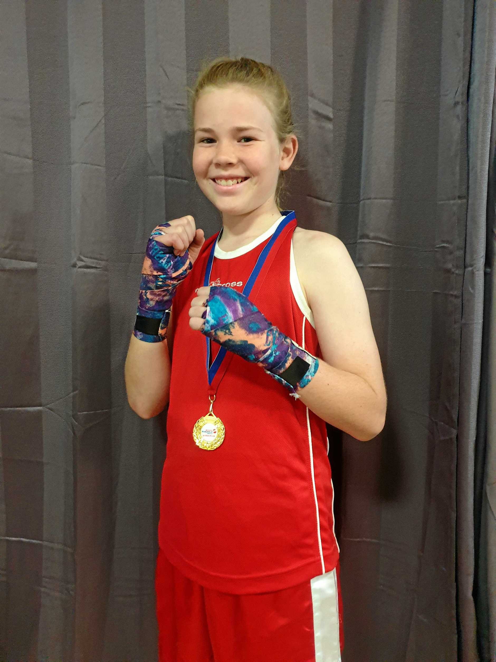 Amelia O'Toole proudly shows off gold medal after gold under-12 38kg B-division.