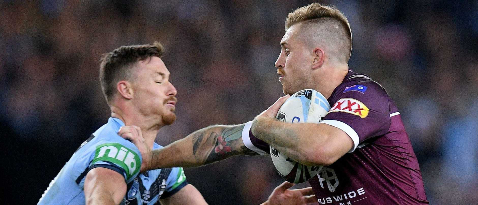 Maroons fullback Cameron Munster fends off a tackle from Blues hooker Damien Cook. Picture: AAP